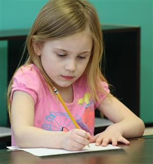 female kindergarten student writing on paper